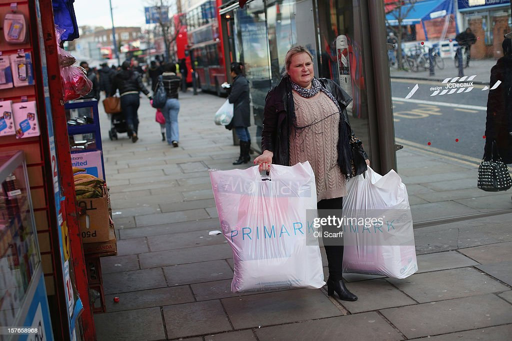 A woman carries shopping bags from a discount fashion retailer along Lewisham high street on December 5, 2012 in London, England. The Chancellor of the Exchequer George Osborne has stated that the United Kingdom's economy is still struggling during his autumn budget statement to Parliament.
