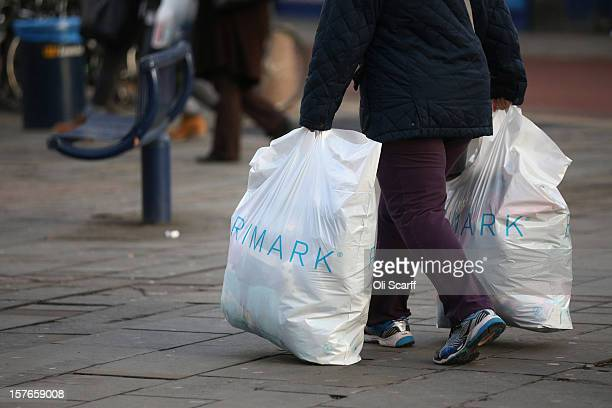 A woman carries shopping bags from a discount fashion retailer along Lewisham high street on December 5 2012 in London England The Chancellor of the...
