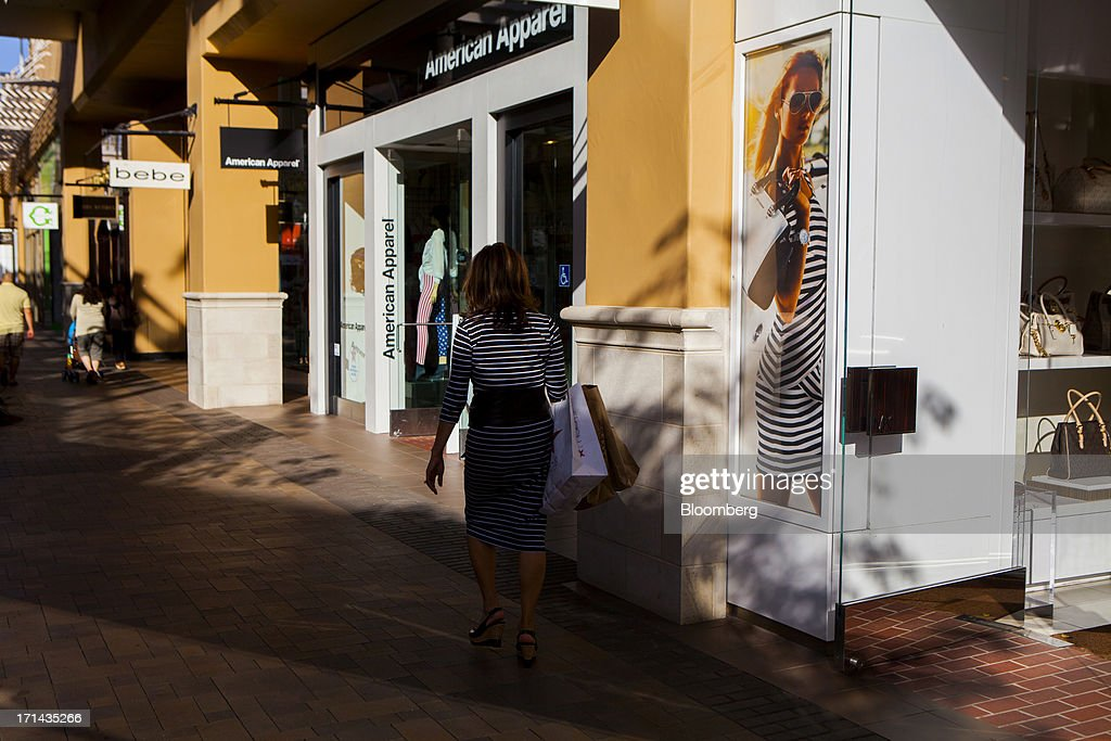 A woman carries shopping bags while walking past an American Apparel Inc. store at the Fashion Valley Mall in San Diego, California, U.S., on Saturday, June 22, 2013. The Bureau of Economic Analysis is schedule to release personal consumption figures on June 26. Photographer: Sam Hodgson/Bloomberg via Getty Images