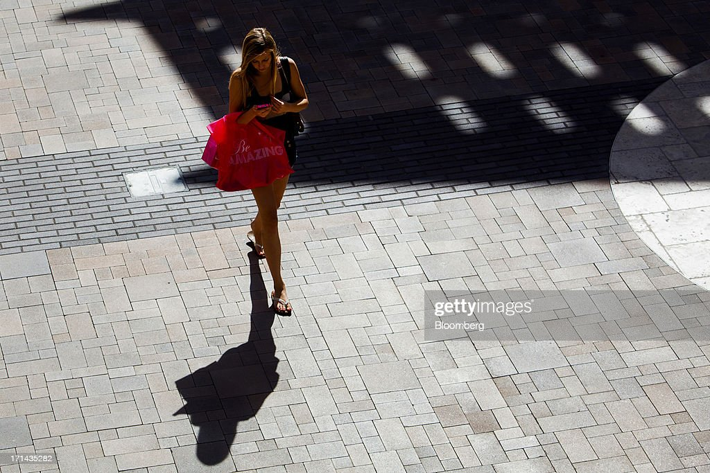A woman carries shopping bags while walking through the Fashion Valley Mall in San Diego, California, U.S., on Saturday, June 22, 2013. The Bureau of Economic Analysis is schedule to release personal consumption figures on June 26. Photographer: Sam Hodgson/Bloomberg via Getty Images