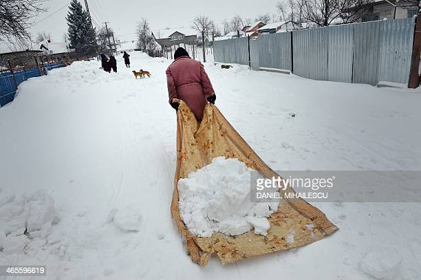 A woman carries snow on a plastic foil outside her home in Smeeni village about 100 kilometers east of Bucharest on January 28 2013 A thick blanket...