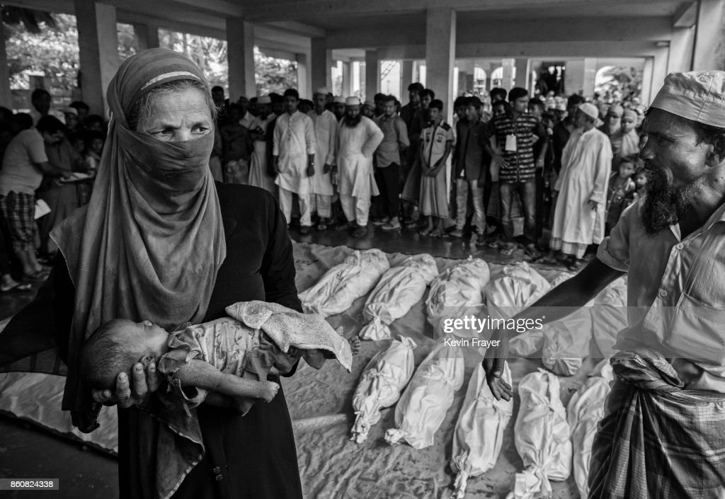 COX'S BAZAR, BANGLADESH - SEPTEMBER 29: A woman carries the body of a Rohingya refugee boy as others are seen wrapped in white sheets prior to burial after they died when their boat capsized while fleeing Myanmar on September 29, 2017 in Cox's Bazar, Bangladesh. More than half a million Rohingya refugees have flooded into Bangladesh to flee an offensive by Myanmar's military that the United Nations has called 'a textbook example of ethnic cleansing'. The refugee population is expected to swell further, with thousands more Rohingya Muslims said to be making the perilous journey on foot toward the border, or paying smugglers to take them across by water in wooden boats. Hundreds are known to have died trying to escape, and survivors arrive with horrifying accounts of villages burned, women raped, and scores killed in the 'clearance operations' by Myanmar's army and Buddhist mobs that were sparked by militant attacks on security posts in Rakhine state on August 25, 2017. What the Rohingya refugees flee to is a different kind of suffering in sprawling makeshift camps rife with fears of malnutrition, cholera, and other diseases. Aid organizations are struggling to keep pace with the scale of need and the staggering number of them - an estimated 60 percent - who are children arriving alone. Bangladesh, whose acceptance of the refugees has been praised by humanitarian officials for saving lives, has urged the creation of an internationally-recognized 'safe zone' where refugees can return, though Rohingya Muslims have long been persecuted in predominantly Buddhist Myanmar. World leaders are still debating how to confront the country and its de facto leader, Aung San Suu Kyi, a Nobel Peace Prize laureate who championed democracy, but now appears unable or unwilling to stop the army's brutal crackdown.
