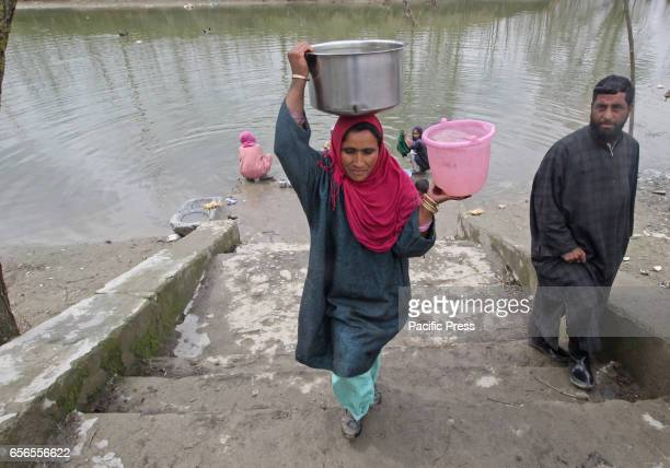 A woman carries water containers because of unavailability of the portable water through taps in Baramulla district
