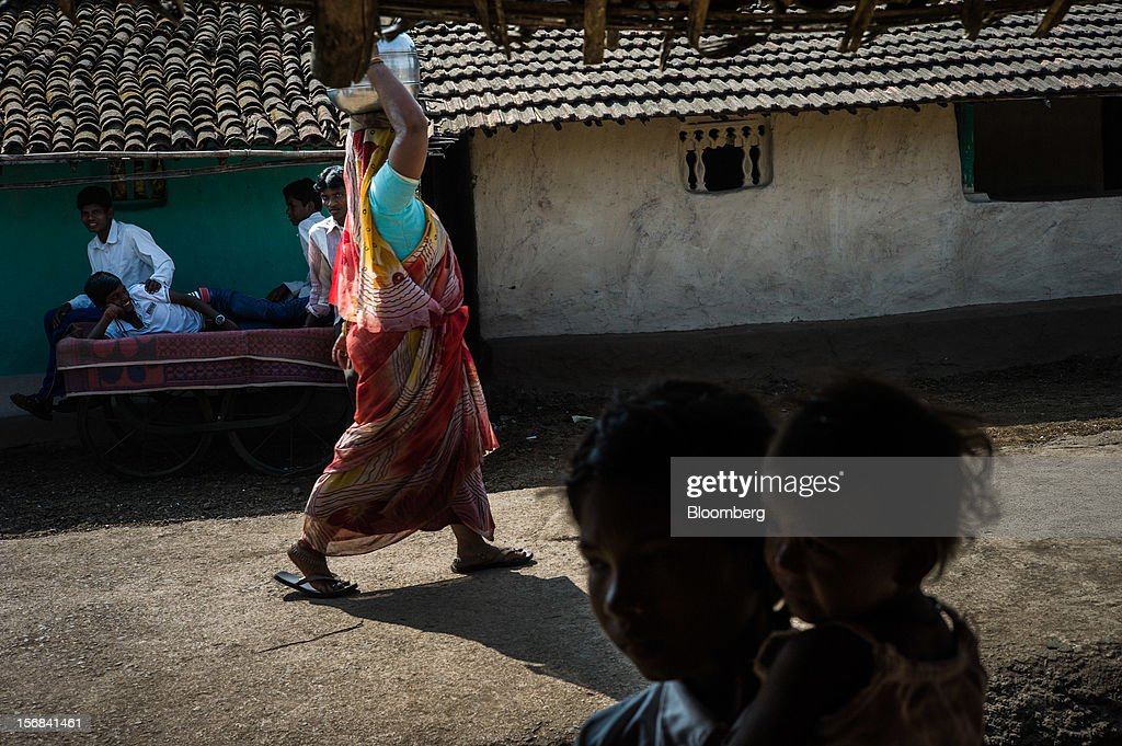 A woman carries water on her head in Semadoh village, Maharashtra, India, on Thursday, Nov. 15, 2012. The Indian economy will expand 4.9 percent in 2012, the least in a decade, according to the International Monetary Fund. Photographer: Sanjit Das/Bloomberg via Getty Images
