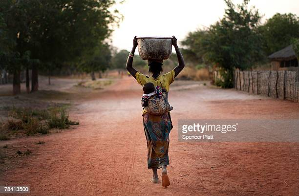 A woman carries water to her home in a rebel held town December 12 2007 in Gordil in the northern Central African Republic Central African Republic...