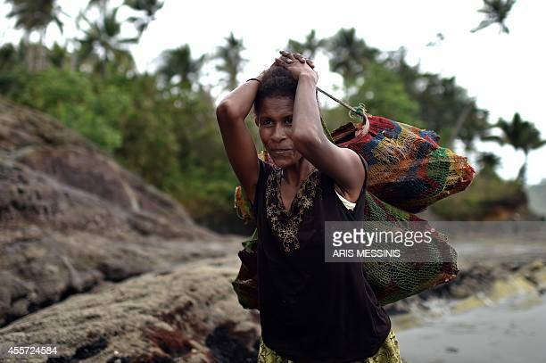 A woman carries wood in a bag in the town of Kerema Papua New Guinea on September 7 2014 AFP PHOTO / ARIS MESSINIS