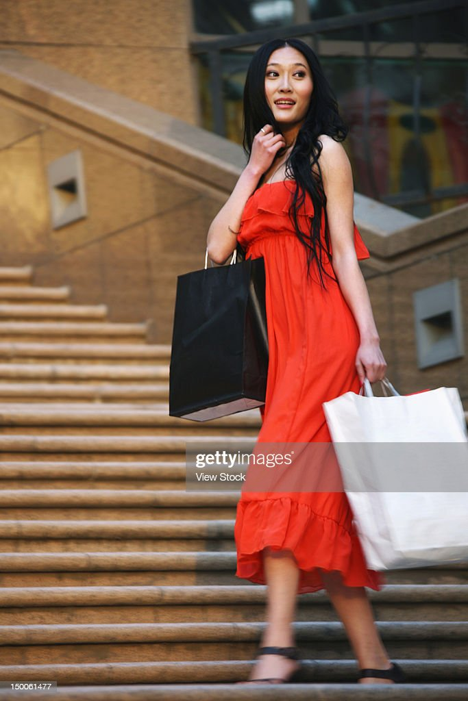 Woman carring shopping bags walking along street : ストックフォト