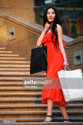 Woman carring shopping bags walking along street : Foto de stock