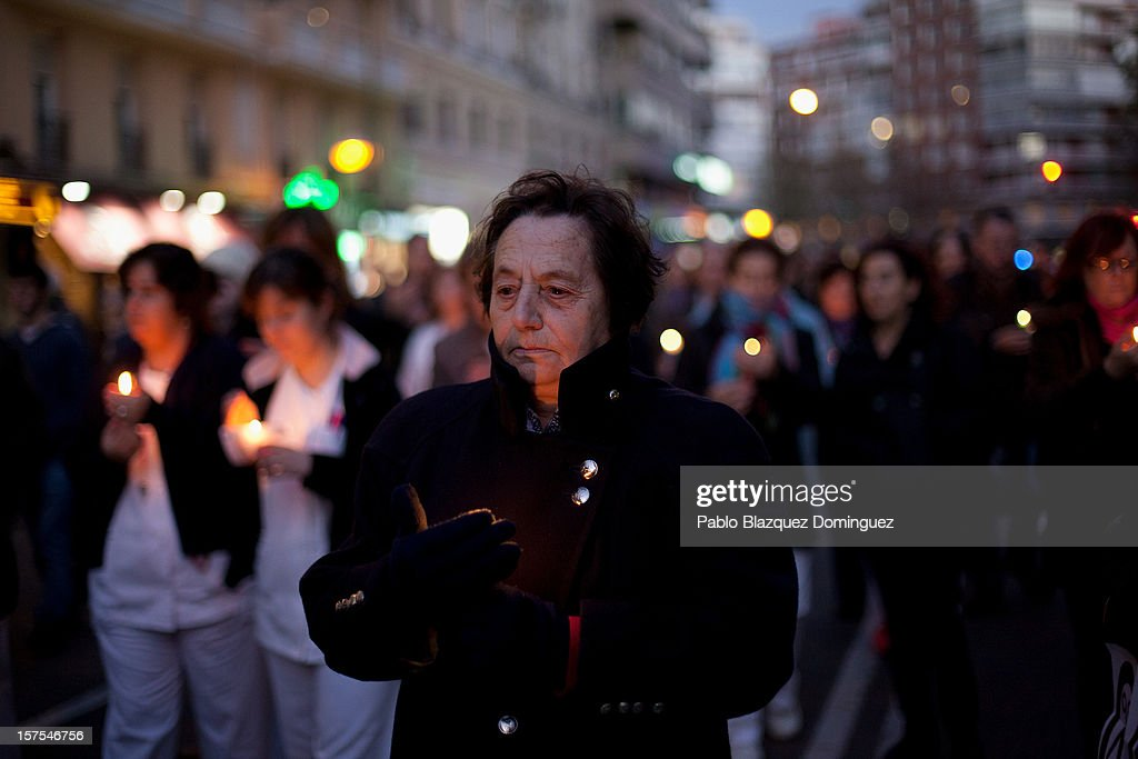 A woman carry a candle amid other health workers during a protest mourning the public health system on December 4, 2012 in Madrid, Spain. Trade unions called for the second 48-hour health workers' strike in the Madrid region, after the regional government announced severe cuts and privatization of medical centers.