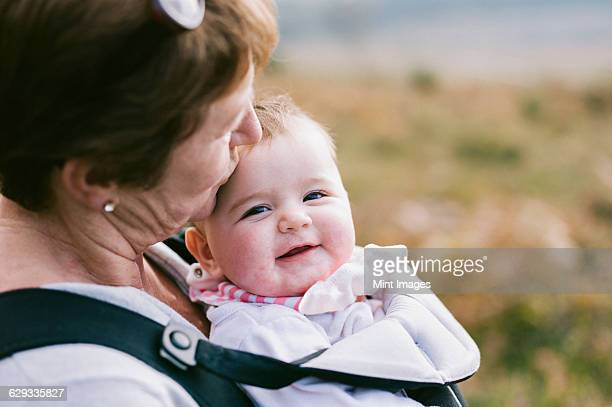 A woman carrying a baby in a baby carrier, kissing her on the head.