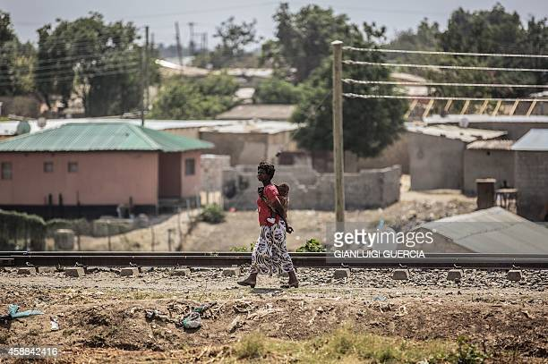 A woman carrying a baby on her back walks next to train tracks in the 'compound' township on the oustkirts of Lusaka on November 12 a day after the...