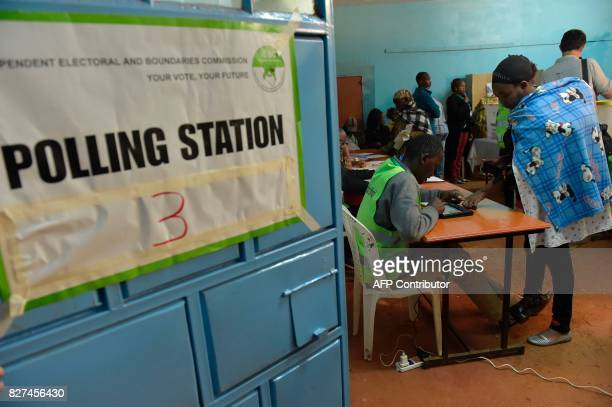 TOPSHOT A woman carrying a baby verify's her identification at a polling station during the August 8 2017 presidential election in Gatundu Kiambu...
