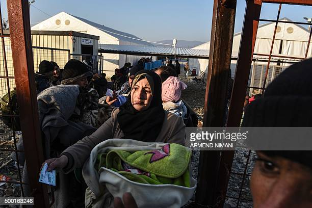 A woman carrying a baby waits with other migrants and refugees to board a train after crossing the GreekMacedonian border near Gevgelija on December...