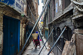 A woman carrying a basket on her back walks down an alley past construction props supporting buildings in Lalitpur Kathmandu Valley Nepal on Thursday...