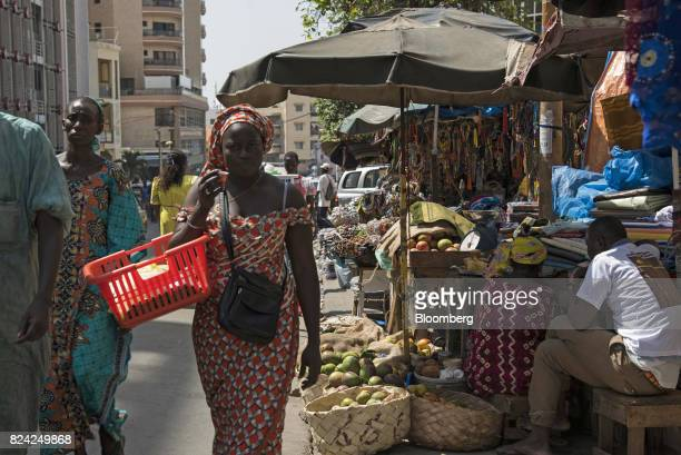 A woman carrying a basket walks by stalls at the Sandaga Market in the Plateau district of Dakar Senegal on Friday July 28 2017 Senegalese voters...