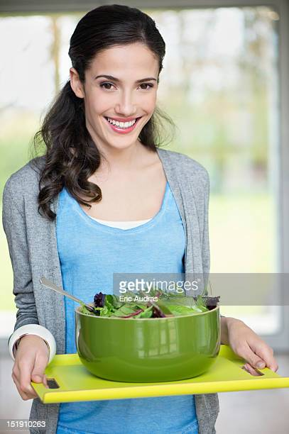 Woman carrying a bowl of salad on a tray