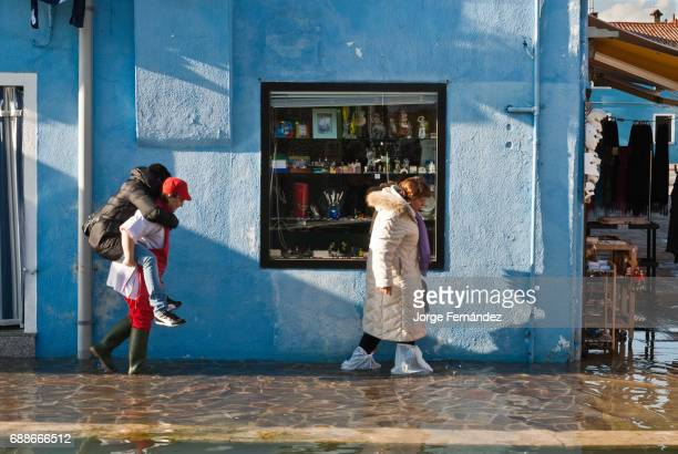 Woman carrying a friend while another walks with plastic bags on her feet on a street flooded by 'acqua alta'