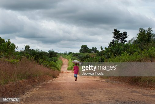 Woman carrying a heavy load on her head in Liberia