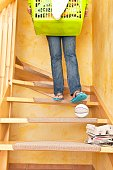 A woman carrying a basket of laundry down the stairs and overlooks a ball, lying on the stairs. Accident and Insurance themes. Risk of home accidents caused by a ball on the stairs, such an accident c
