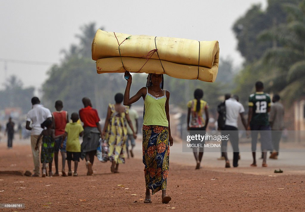 A woman carrying a mattress on her head flees the Gobongo district in Bangui on December 26, 2013. The Red Cross said it had recovered some 40 bodies on the streets of Bangui as the United States expressed alarm at the latest eruption of fighting in the Central African Republic. French troops have beefed up patrols after a bloody Christmas in the strife-torn capital, where more than 1,000 are believed to have been killed in three weeks of conflict between Christians and Muslims.