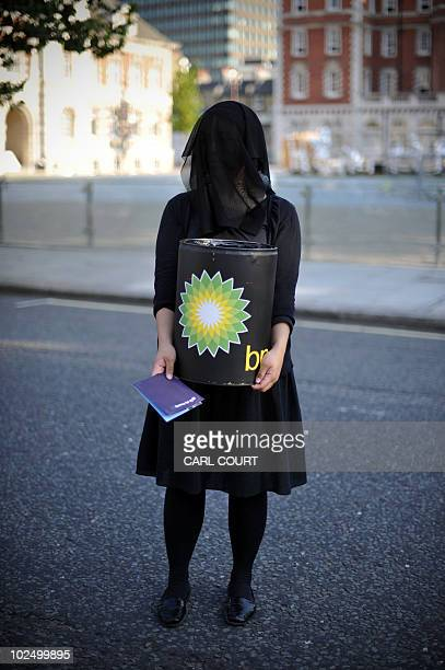 A woman carrying a mock BP oil barrel stands outside the Tate Britain after protesters belonging to a group of artists calling themselves 'The Good...