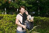 Woman carrying a Pekinese dog in bag