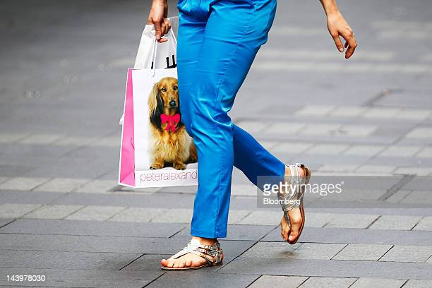 A woman carrying a Peter Alexander shopping bag walks along the Pitt Street shopping mall in Sydney Australia on Saturday May 5 2012 The Australian...