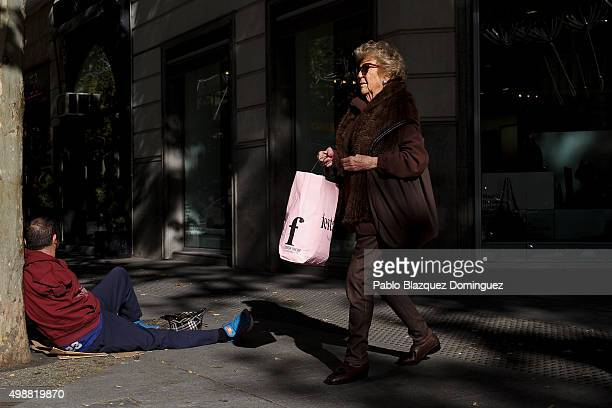 A woman carrying a shopping bag walks past beggar at Calle Serrano which is one of the most expensive streets of Spain on November 26 2015 in Madrid...