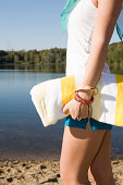Woman carrying a towel near a lake