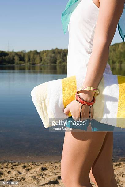 Woman carrying a towel near a lake