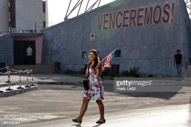 A woman carrying a US flag walks by the US embassy in Havana on July 20 2015 The United States and Cuba formally resumed diplomatic relations Monday...