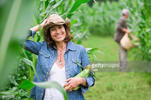 Woman Carrying an Ear of Corn in Field