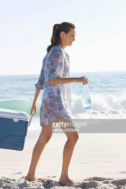 Woman carrying an ice box on the beach