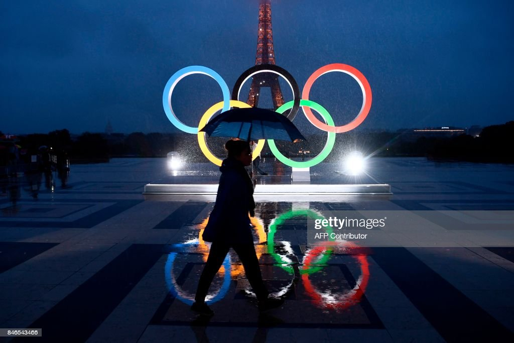 A woman carrying an umbrella walks past the Olympics Rings on the Trocadero Esplanade near the Eiffel Tower in Paris, on September 13, 2017, after the International Olympic Committee named Paris host city of the 2024 Summer Olympic Games. The International Olympic Committee named Paris and Los Angeles as hosts for the 2024 and 2028 Olympics on September 13, 2017, crowning two cities at the same time in a historic first for the embattled sports body. /