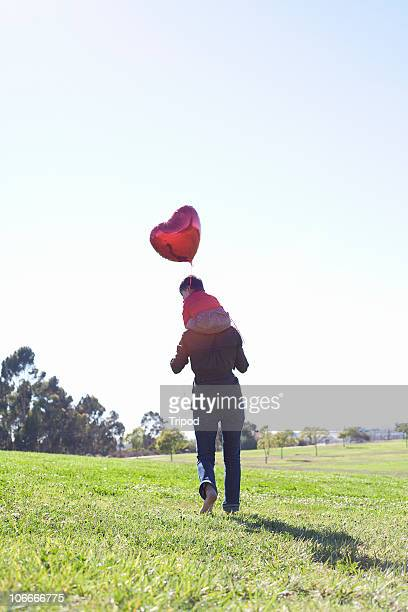 Woman carrying baby with heart balloon