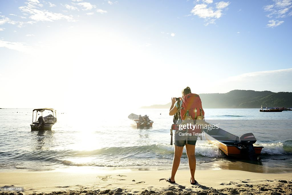 Woman carrying backpack taking photo on beach