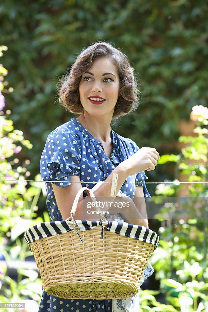 Woman carrying basket in backyard