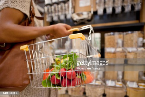 Woman carrying basket in supermarket : Stock Photo
