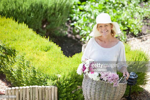 Woman carrying basket of flowers in garden