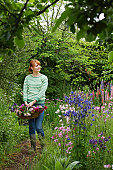 Woman carrying basket of flowers in garden