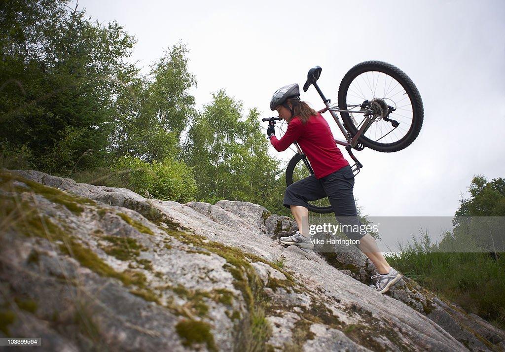 Woman carrying bike  : Stock Photo