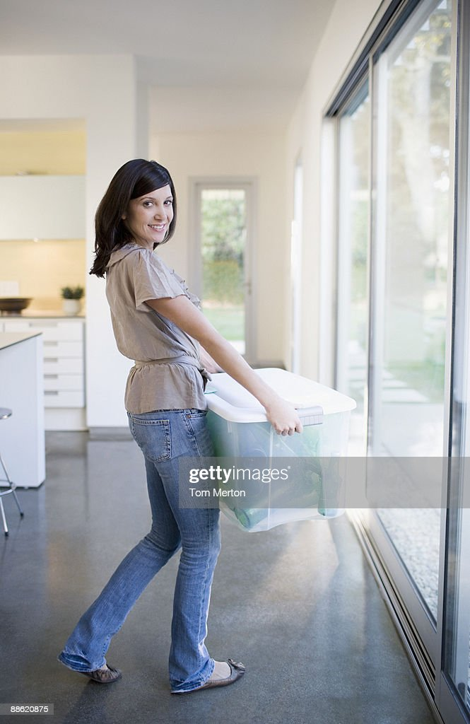 Woman carrying bin of glass bottles : Stock Photo