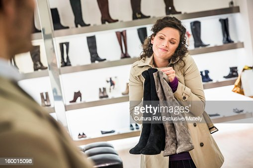 Woman carrying boots in store : Stock Photo