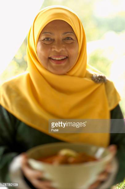 Woman Carrying Bowl of Food