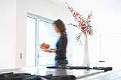 Woman carrying bowl of fruit in kitchen, side view (blurred motion)