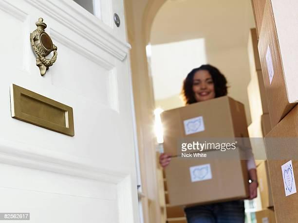 Woman carrying boxes of goods to door