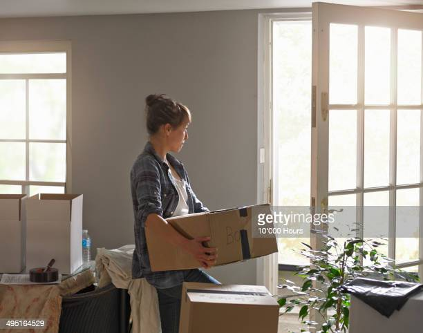 A woman carrying boxes whilst moving home