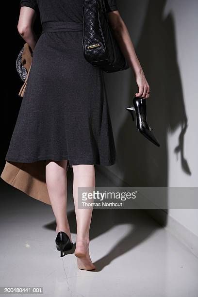 Woman carrying broken high heel, rear view, low section