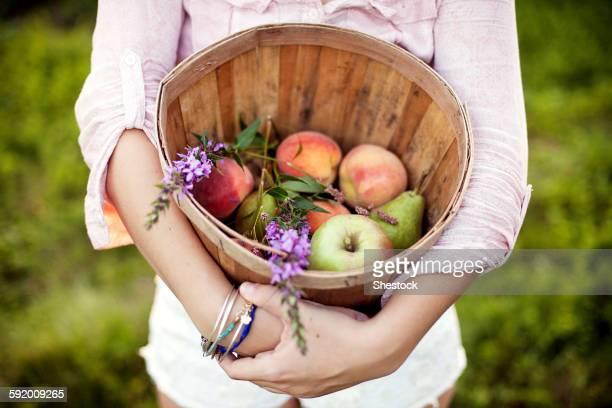 Woman carrying bucket of apples in field