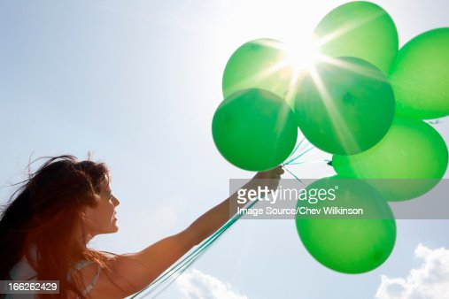 Woman carrying bunch of balloons